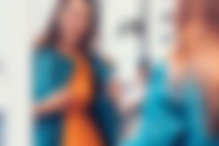 Девушка в оранжевом платье, имитирующем загар, и в синем пальто смотрится радостно в зеркало