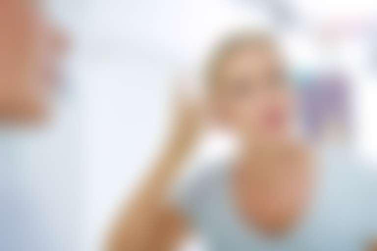 Женщина 50+ с пристрастием рассматривает свое лицо в зеркале
