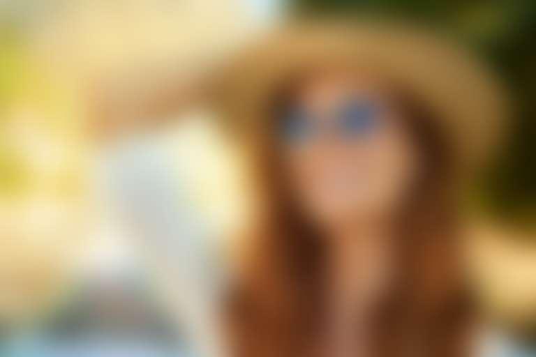 Женщина 40+ в солнцезащитных очках и шляпе улыбается солнцу