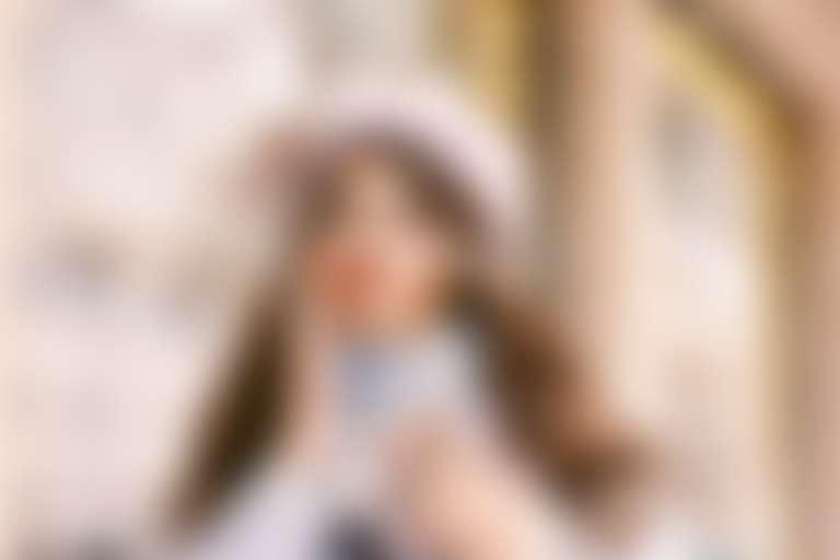 Девушка в белой шапке на фоне новогодних витрин дотрагивается рукой до лица