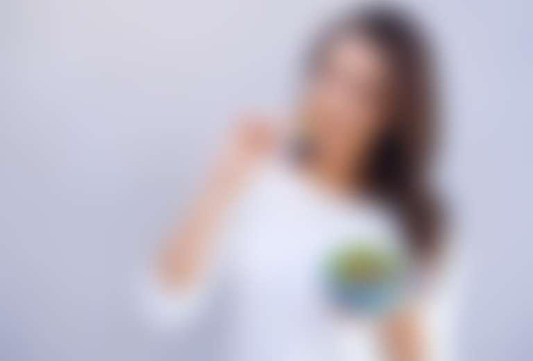 Довольная девушка в белой кофточке держит тарелку с овощами и фруктами и ест оттуда