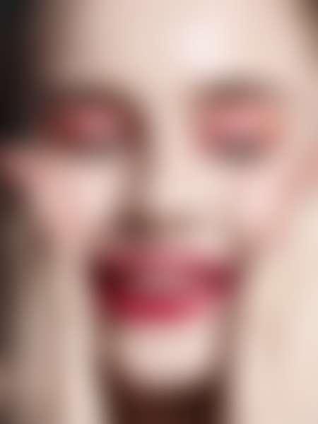 Девушка с красной помадой, красными тенями наносит на лицо крем