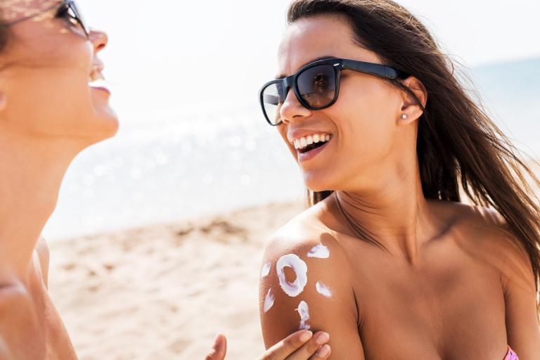 Девушки на пляже наносят санскрин в виде солнышка.