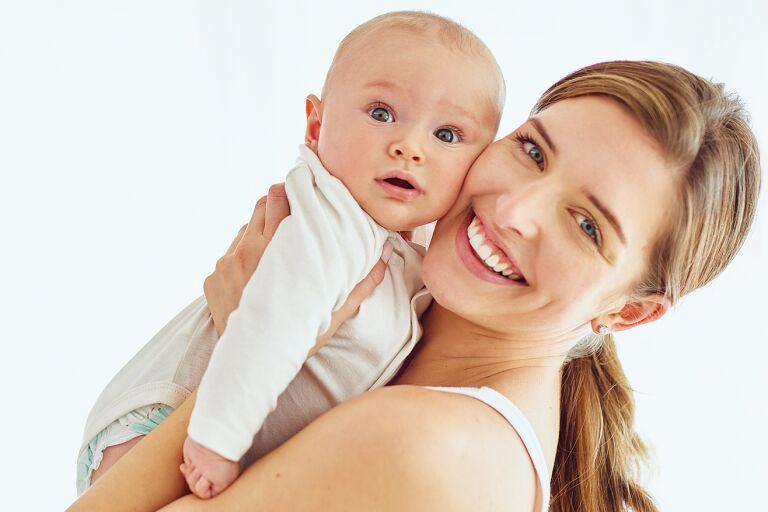 Мама с малышом после водных процедур и нанесения на кожу детского крема