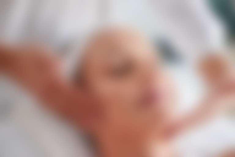Крупно лицо довольной девушки во время косметической процедуры