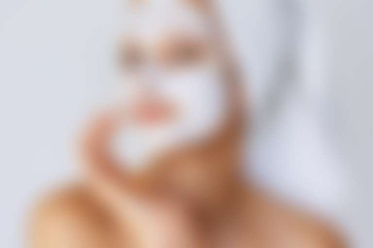 Девушка в белом полотенце на голове и с маской на лице довольно улыбается в кадр
