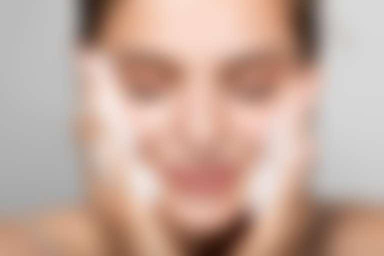 Крупный портрет улыбающейся девушки с закрытыми глазами, приставила к лицу руки в пенке