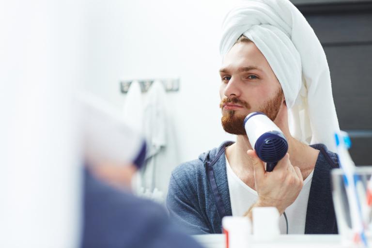 Парень с полотенцем на голове сушит рыжую бороду феном