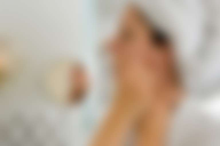Девушка перед зеркалом удаляет усики с помощью восковых полосок