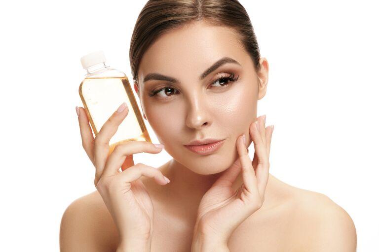Девушка держит в руках бутылочку с косметическим маслом