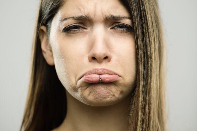Симпатичная шатенка с пирсингом на губе кривит рот в скорбной гримасе, образуя морщины марионетки