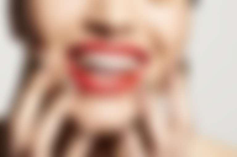 Нижняя половина лица улыбающейся девушки с красной прмадой, приложившей пальцы к подбородку