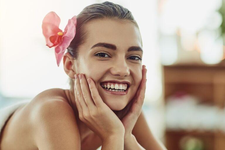 Улыбающаяся девушка с орхидеей в волосах лежит в белом полотенце в салоне