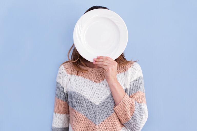 Девушка в полосатой свитере прикрывает лица белой тарелкой