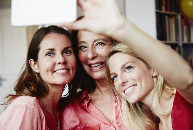Три женщины разного возраста улыбаются в кадре