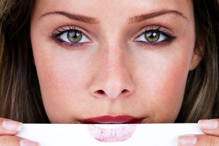 Девушка закрывает нижнюю губу белой бумагой с отпечатком помады
