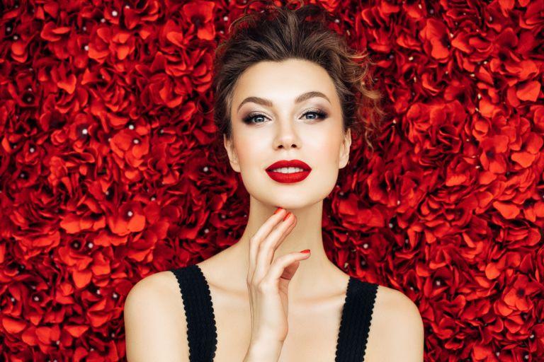 Девушка с вечерним макияжем на фоне красных цветов