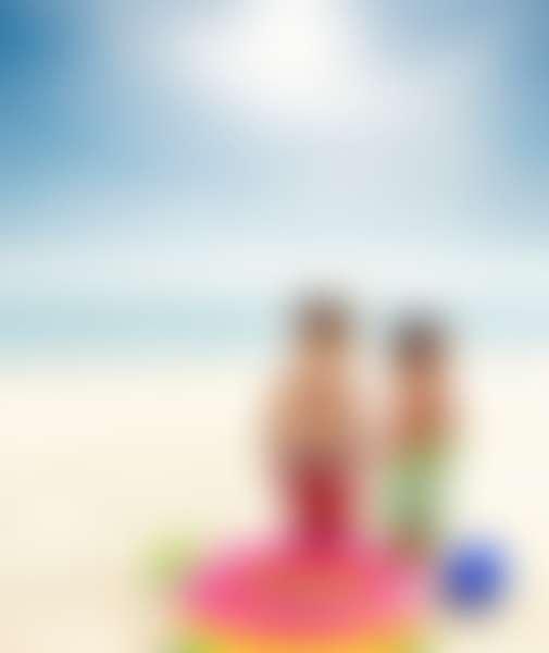 Двое мальчиков без футболок и головных уборов на берегу моря
