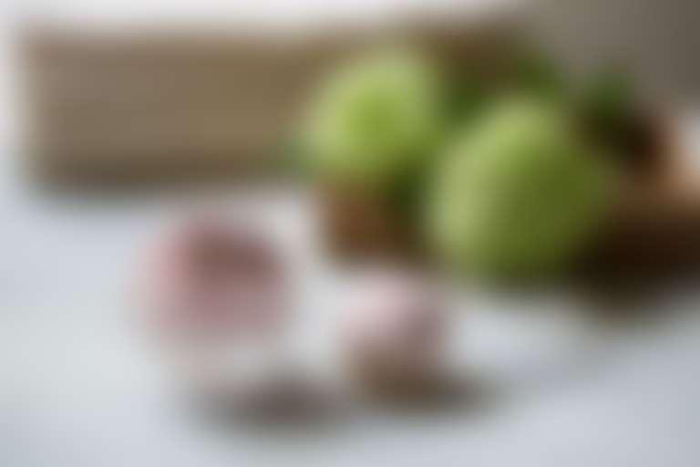 На столе разложены составляющие для приготовления альгинатной маски: порошок, цветы и тд