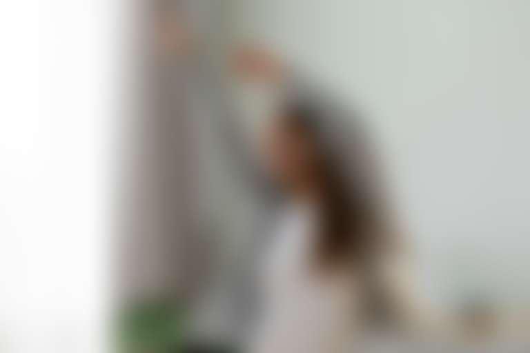 Девушка в наушниках танцует у себя дома