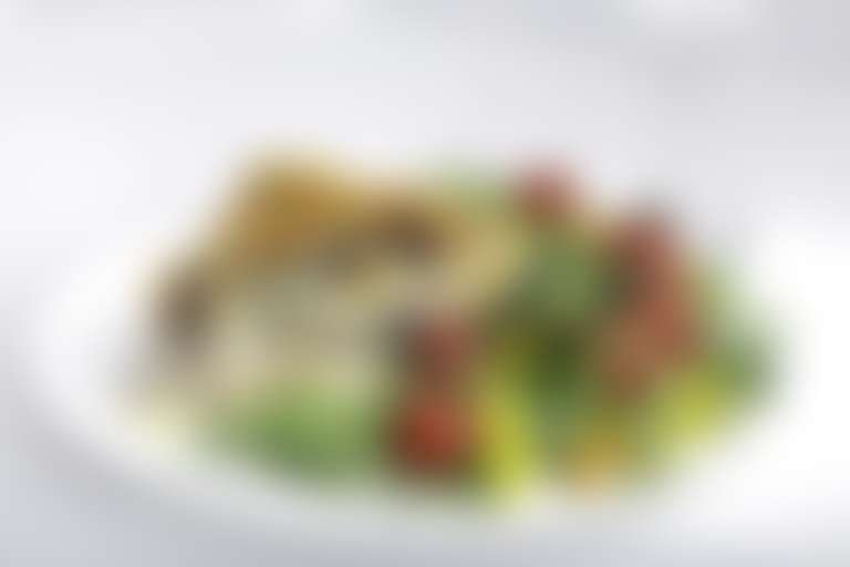 Кусок киша с овощами на тарелке