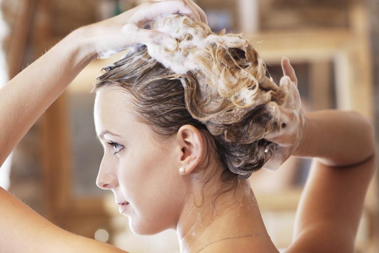 Девушка намыливает голову шампунем