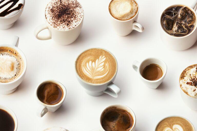 На столе расставлены чашки с разнообразными видами кофе: капучино, эспрессо, латте и тд.