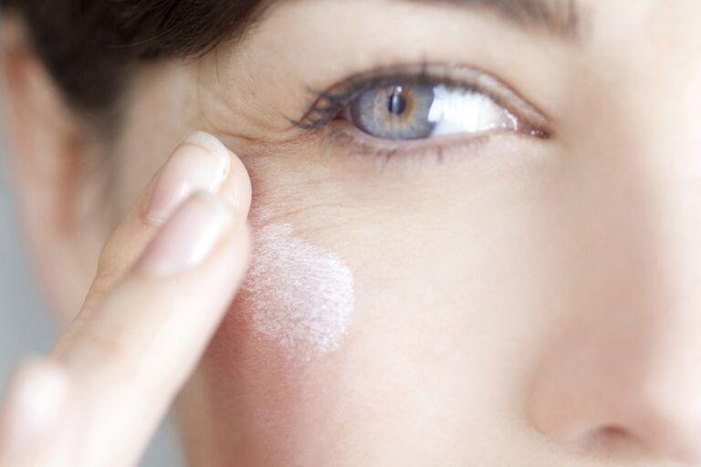 Женщина с морщинками в уголках глаз наносит крем