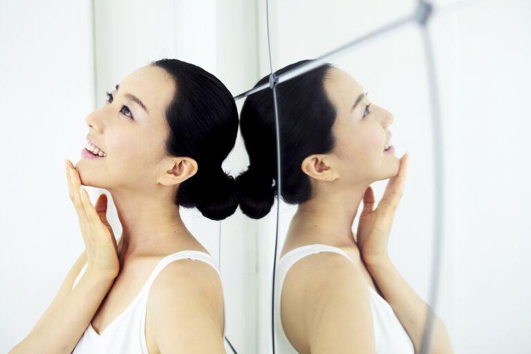 Девушка у зеркала трогает руками свое лицо