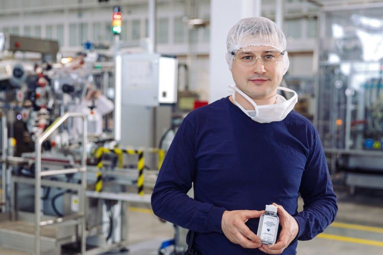 мужчина с медицинской маской держит санитайзер для рук лореаль на Калужском заводе лореаль