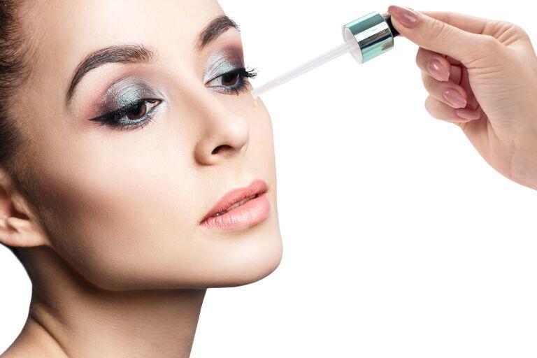 Девушка с ярким макияжем глаз наносит средство на нижнее веко из пипетки