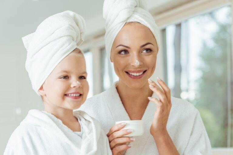 Женщина и ребенок в белых халатах и тюрбанах с кремом на носах