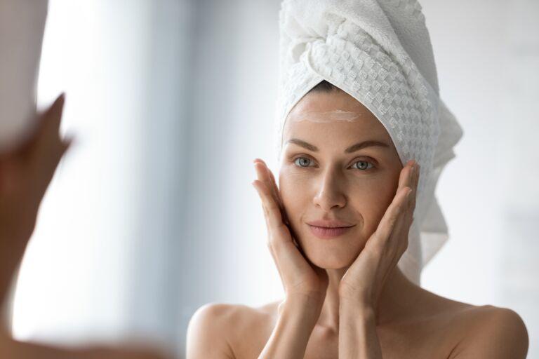 женщина в тюрбане из полотенца смотрится в зеркало на лбу крем