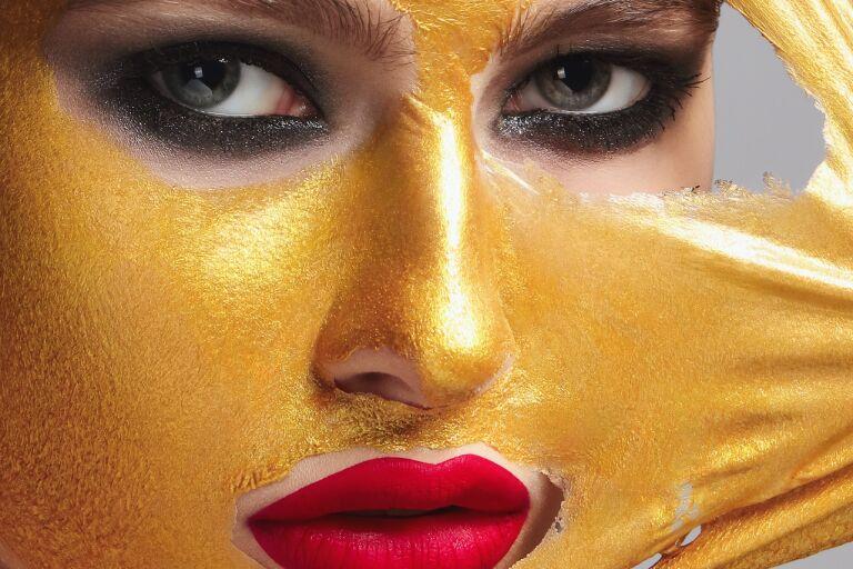 Девушка с густо подведенными черным глазами и ярко-красной помадой снимает золотистую маску-пленку
