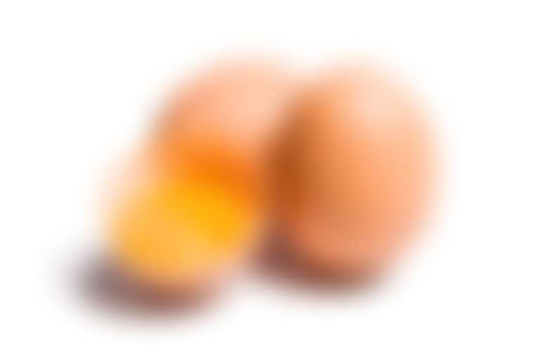 Три яйца, одно из них разбито, виден желток