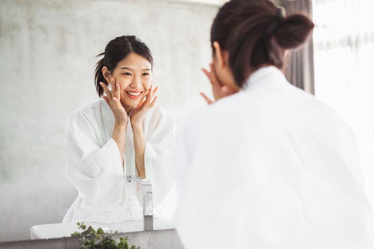 Девушка перед зеркалом делает классический массаж лица