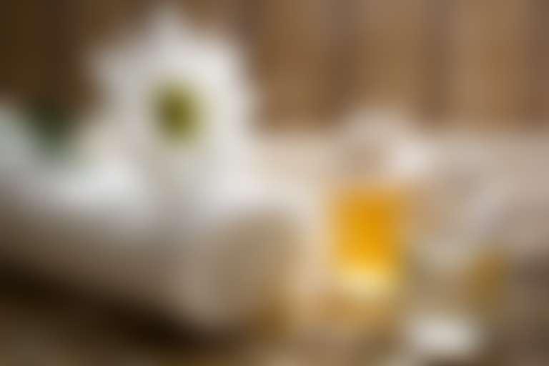 Две бутылочки с прозрачной и желтой жидкостями и свернутое полотенце с цветком ромашки