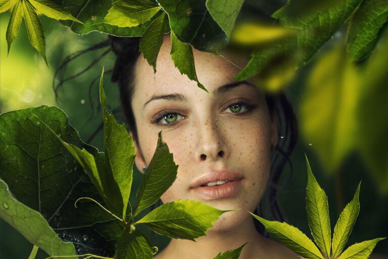 Девушка в тени зеленых листьев после маски для лица из ламинарии