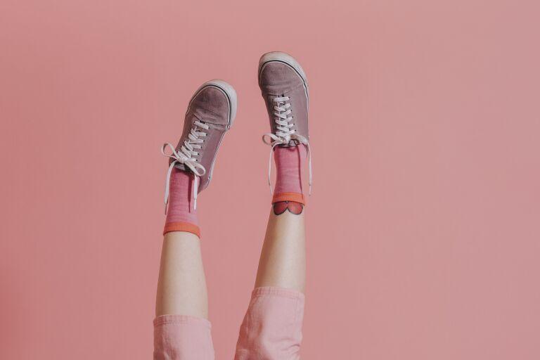 На розовом фоне - ноги девушки в коротких розовых джинсах капри, розовых носках и брусничных кедах с белыми шнурками
