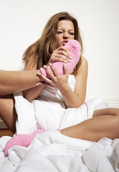 Девушка нюхает свою ногу в розовом носке и морщится