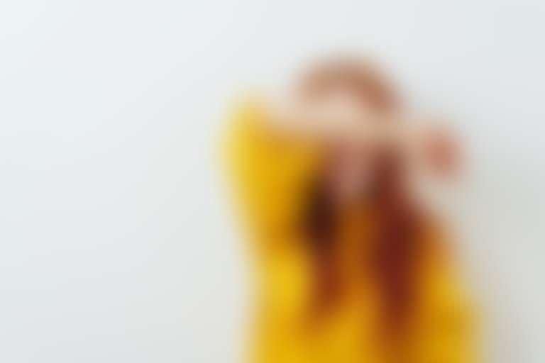 Девушка в желтом свитере закрывает рукой глаза