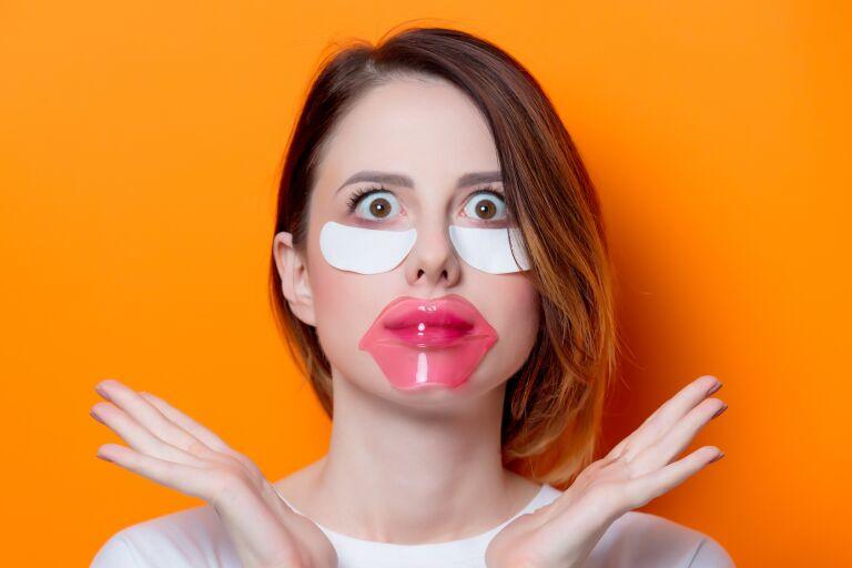 Девушка на оранжевом фоне с вытаращенными глазами и наклеенными патчами под глаза и на губы