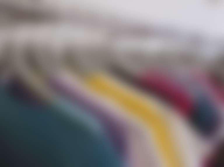 Много разноцветных футболок на вешалках