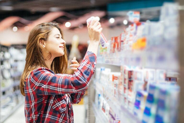 Девушка в клетчатой рубашке с длинными волосами выбирает в магазине солнцезащитное средство
