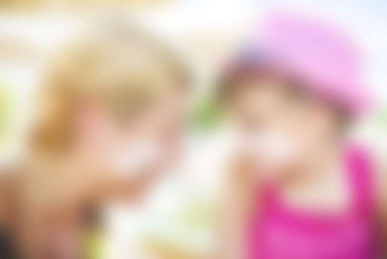 Мама с дочкой намазали на лицо солнцезащитный крем, смотрят друг на друга и улыбаются