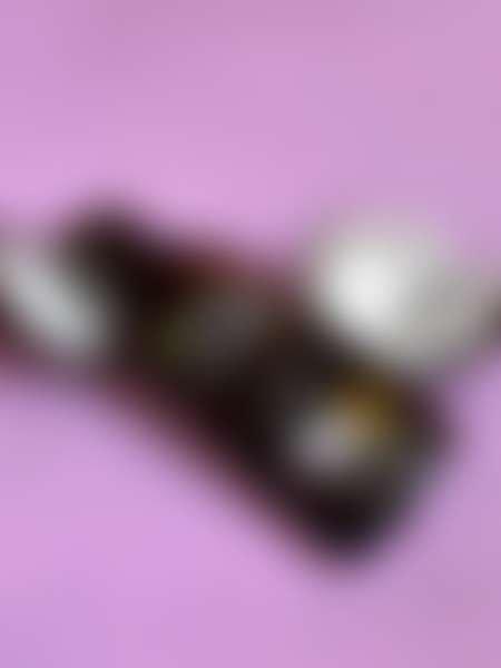 Бутылка с маслом для интенсивного загара и половинками кокоса на розовом фоне