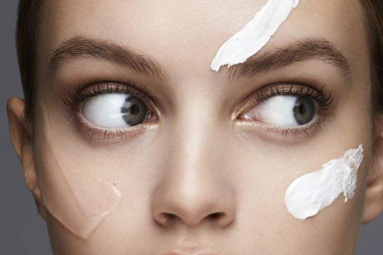 удивленная девушка с ухоженной кожей и полосками кремов на лице