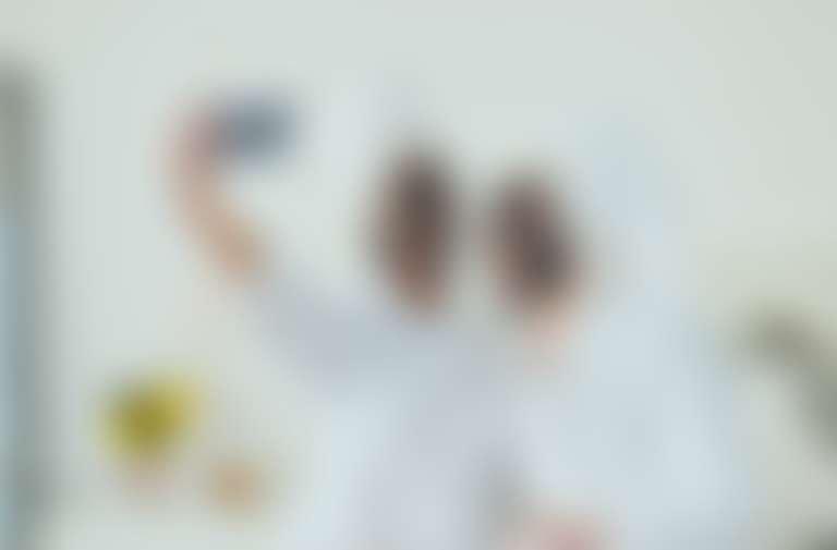 две девушки с черными косметическими масками на лице делают селфи