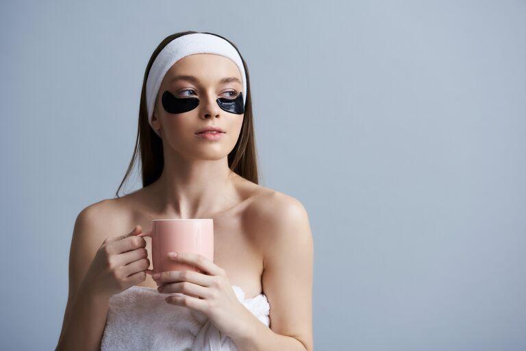 Девушка с маской от синяков под глазами — черными патчами на нижних веках