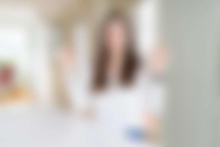 Темноволосая девушка в белом делает гимнастику бодифлекс (упражнения для лица и шеи), сидя за столом